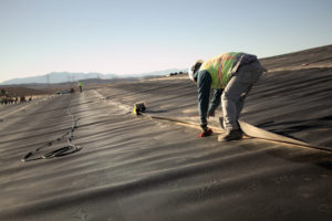 Image of worker applying geomembrane lining